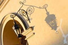 La lanterna in ferro battuto fonde un'ombra su una parete immagine stock libera da diritti