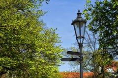 La lanterna nera del metallo con due turistici firma dentro un parco verde Immagine Stock Libera da Diritti