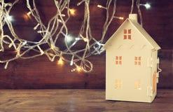 La lanterne blanche de maison avec les bougies brûlantes à l'intérieur devant l'or de guirlande s'allume sur la table en bois rét Images libres de droits
