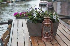 La lanterne de cuivre est sur la table en bois avec des fleurs Image libre de droits