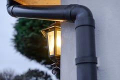 La lanterne de sécurité vue s'est allumée pendant le crépuscule en dehors d'une grande maison photos stock