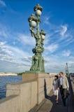 La lanterne triple sur le pont et les personnes de Troitskiy (trinité) marchant le long du pont Images libres de droits
