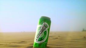 La lata de cerveza verde de Tuborg colocada entre las arenas del desierto en una luz del sol, anuncio del tuborg, producto verde  almacen de metraje de vídeo
