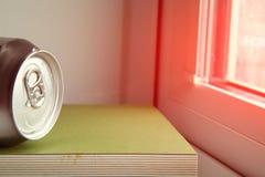 La latta mettere sopra il libro verde della copertura accanto alla finestra Immagine Stock