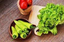 La lattuga, i pomodori ed i peperoni sono disposti insieme in una ciotola sulla a Fotografie Stock