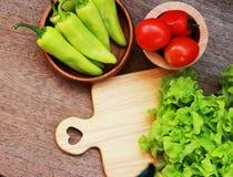 La lattuga, i pomodori ed i peperoni sono disposti insieme in una ciotola sulla a Fotografie Stock Libere da Diritti
