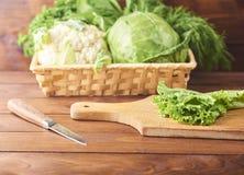 La lattuga va sul tagliere con il coltello su fondo di legno fotografia stock