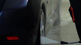 La lavadora del coche lava el coche Un trabajador del t?nel de lavado lava un coche con agua Primer almacen de metraje de vídeo