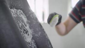 La lavadora está rociando espuma en una tapicería de asientos dentro del automóvil y está frotando por el cepillo, en un garaje,  almacen de metraje de vídeo