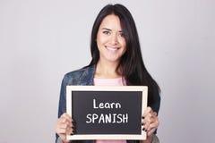 La lavagna della tenuta della giovane donna che dice impara lo Spagnolo Fotografia Stock