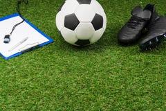 La lavagna per appunti con pallone da calcio e gli stivali su erba lanciano Immagine Stock Libera da Diritti