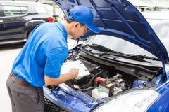 La lavagna per appunti della tenuta dell'uomo del meccanico e controlla l'automobile Immagine Stock