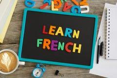 La lavagna scura con impara il consiglio francese dalle lettere di plastica colourful fotografia stock libera da diritti
