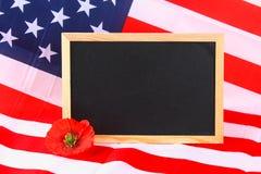 la lavagna sulla bandiera americana e un papavero fioriscono il fondo Fotografia Stock Libera da Diritti