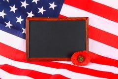 la lavagna sulla bandiera americana e un papavero fioriscono il fondo Fotografie Stock Libere da Diritti