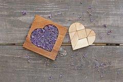 La lavande dans la boîte en forme de coeur en bois et le tangram déconcertent dans la forme de coeur Photos libres de droits