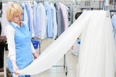 La lavanderia del lavoratore della ragazza guarda e controlla di Tulle bianca e pura Immagine Stock Libera da Diritti