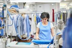 La lavanderia del lavoratore rivestita di ferro copre il ferro asciutto Immagini Stock