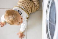 La lavatrice bianca tiene occupato il piccolo neonato immagini stock
