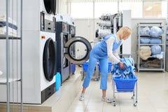 La lavoratrice carica l'abbigliamento della lavanderia nella lavatrice Fotografia Stock