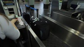 La lavoratrice dell'aeroporto sta mettendo l'etichetta di bagaglio sulla borsa video d archivio