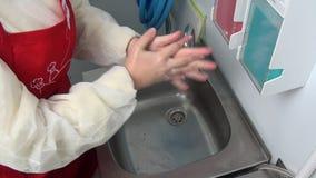 La lavoratrice in grembiule rosso si lava le sue mani sotto il rubinetto video d archivio