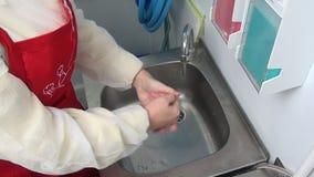La lavoratrice in grembiule rosso si lava le sue mani sotto il rubinetto archivi video