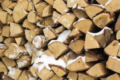 La leña tajada abre una sesión una pila con nieve Imágenes de archivo libres de regalías