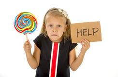La lecca-lecca e l'aiuto della tenuta del bambino abbastanza piccolo firmare dentro i bambini zuccherano l'eccesso Fotografie Stock Libere da Diritti