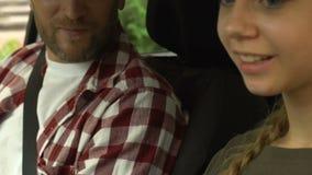 La lección de conducción, instructor enseña a la muchacha adolescente a conducir el coche, seguro auto metrajes