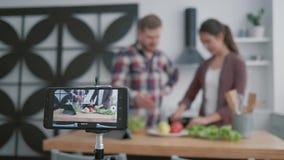La lección en línea a los bloggers culinarios, felices individuo y la muchacha enseñan a suscriptores a cocinar la comida útil de metrajes