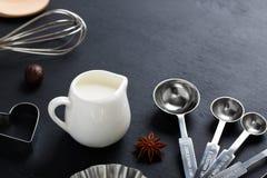 La leche de la hornada, bate, los anis de los cortadores de la galleta de las cucharas dosificadoras Fotos de archivo libres de regalías