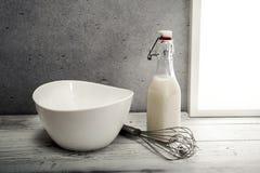 La leche fresca, la botella poner crema, el cuenco y el alambre baten en travesaño de la ventana Fotografía de archivo