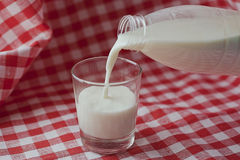 La leche natural se vierte de una botella en un vidrio Foto de archivo