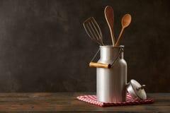 La leche retra puede con artículos de cocina en la tabla de madera Fotografía de archivo