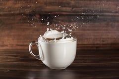 La leche salpica la taza imagenes de archivo
