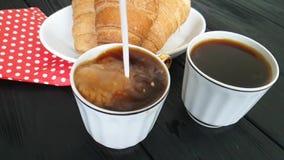 La leche se vierte en una taza de café, desayuna un cruasán metrajes