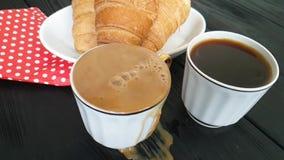 La leche se vierte en una taza de café, un cruasán almacen de video