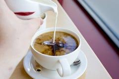 La leche vertió en el café Foto de archivo libre de regalías