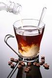 La leche vertió en la taza de café Foto de archivo libre de regalías