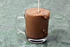 La leche vertió encima de una taza de café sólo Foto de archivo libre de regalías