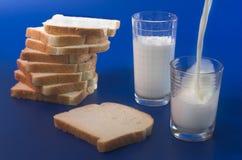 La leche vierte en un vidrio Fotos de archivo