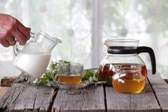 La leche vierte una taza transparente con té Fotografía de archivo libre de regalías