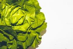 La lechuga verde jugosa fresca en blanco pintó la tabla de madera Foto de archivo libre de regalías