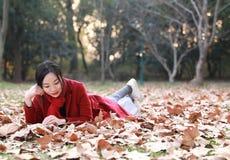 La lectura adentro de la naturaleza es mi afición, muchacha hermosa leyó el libro que miente en las hojas caidas en parque del ot Imagen de archivo libre de regalías
