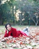 La lectura adentro de la naturaleza es mi afición, muchacha hermosa leyó el libro que miente en las hojas caidas en parque del ot Fotografía de archivo