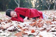 La lectura adentro de la naturaleza es mi afición, muchacha hermosa leyó el libro que miente en las hojas caidas en parque del ot Fotos de archivo libres de regalías