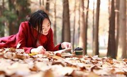 La lectura adentro de la naturaleza es mi afición, muchacha leyó un libro en las hojas caidas Fotografía de archivo libre de regalías