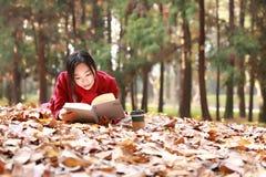 La lectura adentro de la naturaleza es mi afición, muchacha leyó un libro en las hojas caidas Imagenes de archivo