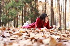 La lectura adentro de la naturaleza es mi afición, muchacha leyó un libro en las hojas caidas Foto de archivo libre de regalías